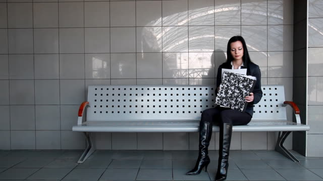 Businesswoman reads documents sitting at the station