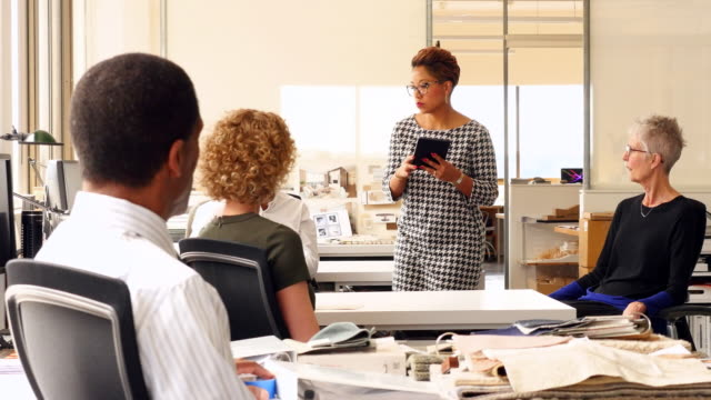 MS Businesswoman referencing digital tablet during meeting with colleagues in office