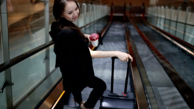 businesswoman rides escalator wearing her suitcase - escalator stock videos & royalty-free footage