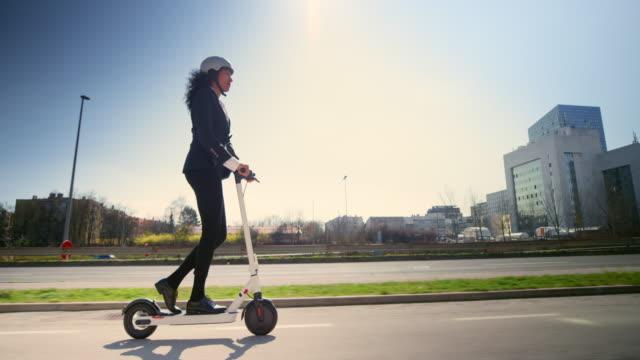 vídeos de stock e filmes b-roll de ts businesswoman riding an e-scooter in the city on a sunny morning - capacete