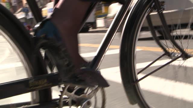 cu pov la ts businesswoman riding bike in city, new york city, new york, usa - montare video stock e b–roll