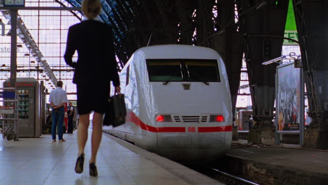 Businesswoman running after train on platform / throwing down briefcase as train leaves / Frankfurt