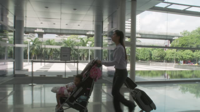 ms pan businesswoman running, pushing daughter (2-3) in baby stroller through lobby / bangkok, thailand - urgency stock videos & royalty-free footage