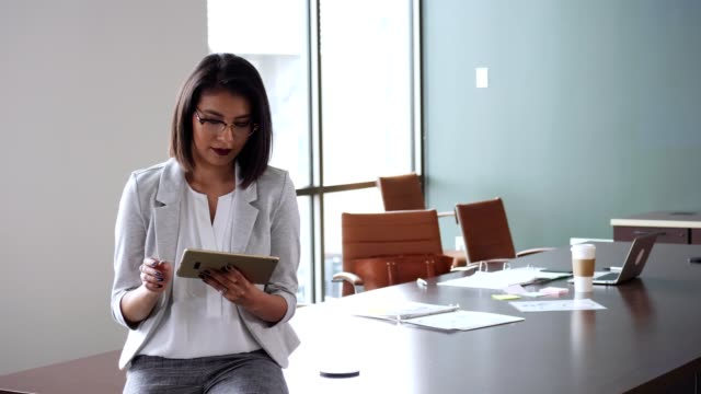 businesswoman scrolls through email on digital tablet - reading glasses stock videos & royalty-free footage