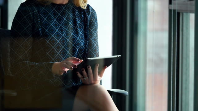 MS Businesswoman seated in office conference room working on digital tablet