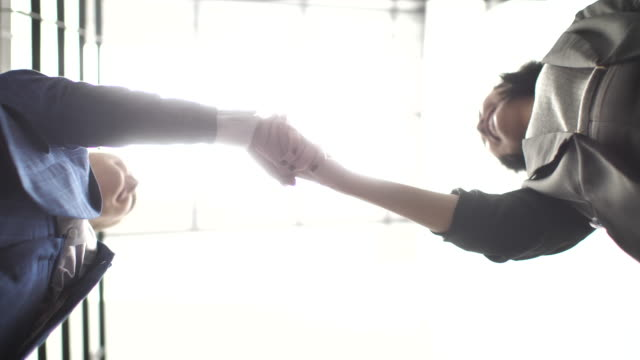 vidéos et rushes de femme d'affaires, se serrant la main au bureau, faible angle de vue - engagement des employés