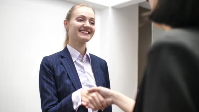 vidéos et rushes de femme d'affaires, se serrant la main au bureau - engagement des employés