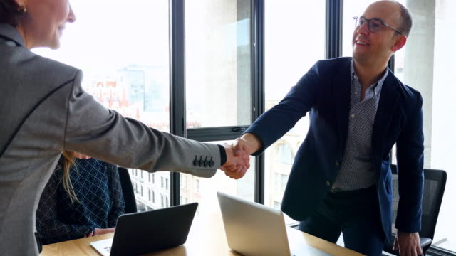ms ts businesswoman shaking hands with businesswoman and businessman before meeting in office conference room - agreement stock videos & royalty-free footage