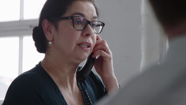businesswoman sharing project details with client over a phone call - landline phone stock videos & royalty-free footage