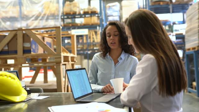 vidéos et rushes de femme d'affaires partageant le niveau de stock d'entrepôt avec le gestionnaire - être debout