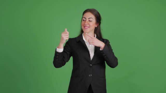 businesswoman showing copy space in hand on green background - kharkov stock videos & royalty-free footage