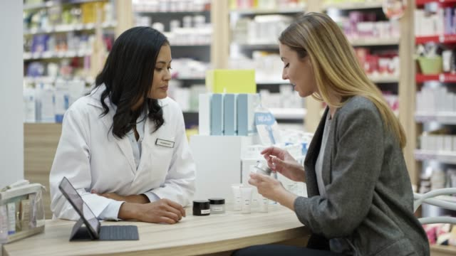 businesswoman showing medical samples to pharmacist - pharmacy stock videos and b-roll footage