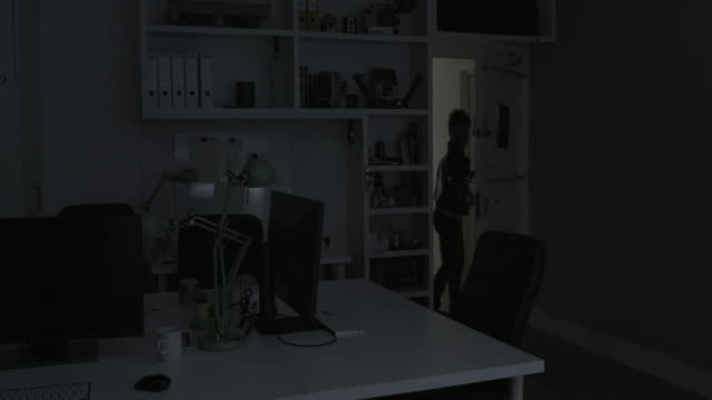 Businesswoman shutting office for the night - wide shot