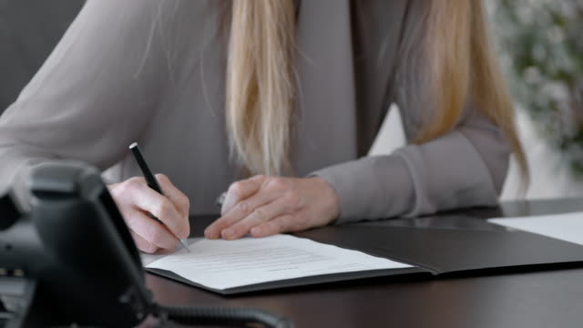 Businesswoman signing a document in her office