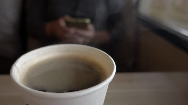 businesswoman sit with hot coffee and use smart phone - blurred motion stock videos & royalty-free footage