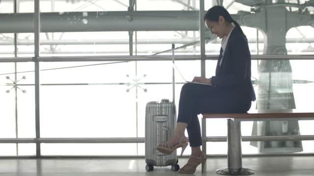 Businesswoman sitting and using Laptop in Airport