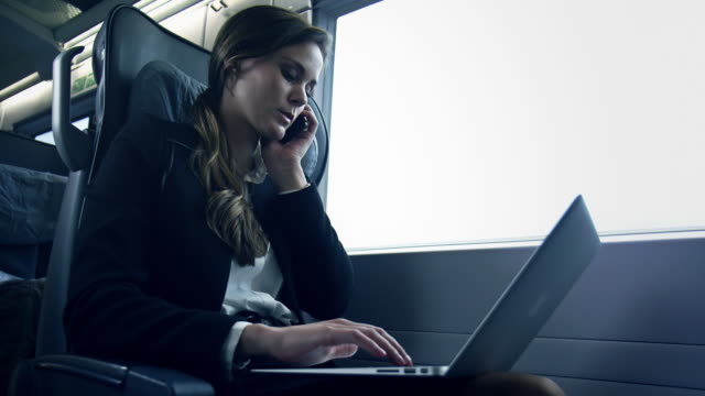 businesswoman sitting and working in train - voice stock videos & royalty-free footage