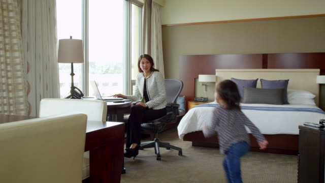 ms businesswoman sitting at desk in hotel room working on laptop. - pillow stock videos and b-roll footage