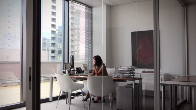ws businesswoman sitting at desk in office looking out window/seattle, washington, usa - pc video stock e b–roll