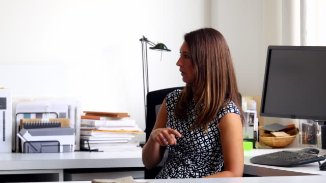 MS Businesswoman sitting at office workstation in discussion with coworker
