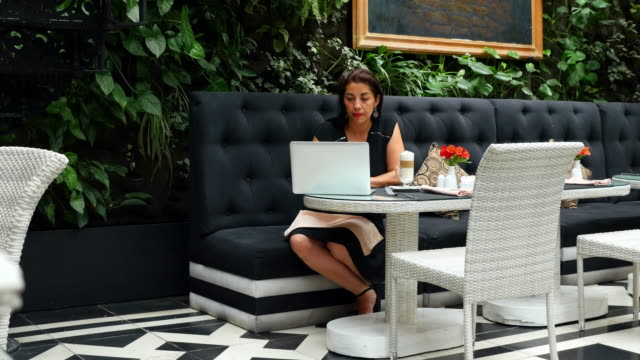 ms businesswoman sitting at table in restaurant drinking coffee and working on laptop - independence stock videos & royalty-free footage