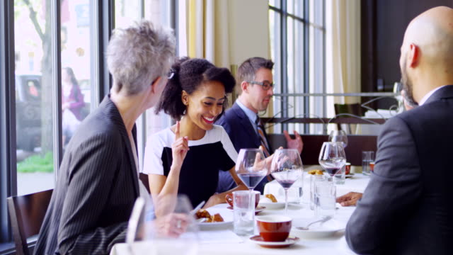 MS businesswoman sitting at table in restaurant listening to business executive during meeting