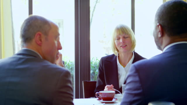 ms businesswoman sitting at table in restaurant listening to colleagues in meeting. - formal businesswear stock videos & royalty-free footage