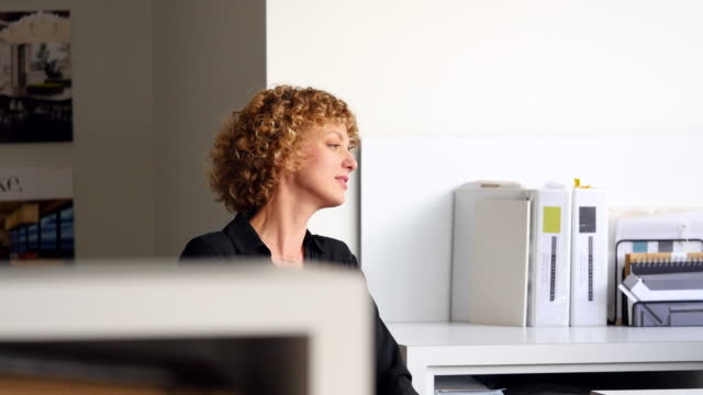 MS Businesswoman sitting at workstation in discussion with colleague