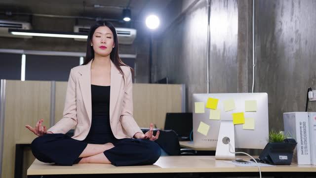 stockvideo's en b-roll-footage met businesswoman sitting in lotus pose on table while meditating in office - in kleermakerszit
