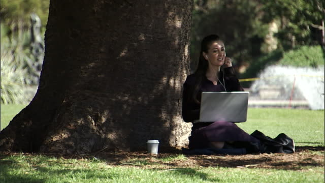 ms, businesswoman sitting on lawn in park, working on laptop and listening mp3 player, sydney, australia - multitasking stock videos & royalty-free footage