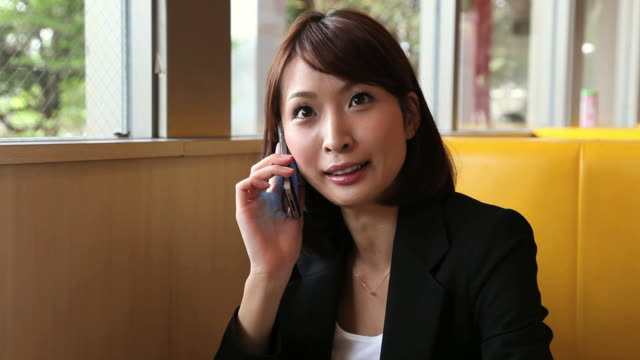 MS Businesswoman sitting on sofa and using smart phone / Odaiba, Tokyo, Japan