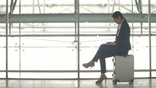 stockvideo's en b-roll-footage met zakenvrouw zittend op koffer met laptop in luchthaven - werkneemster