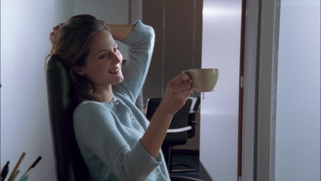 A businesswoman smiles while sitting and holding a coffee cup in her office.