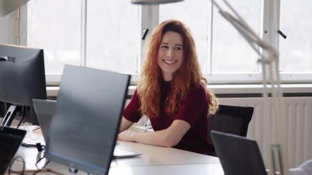 vídeos y material grabado en eventos de stock de una empresaria sonriendo mientras trabaja en su escritorio - aprendiz