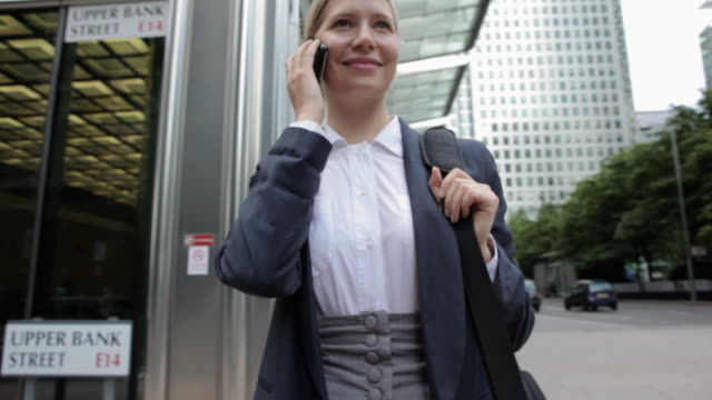 businesswoman speaking on cellphone in city street - ブラウス点の映像素材/bロール