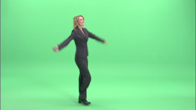 ms, businesswoman spinning around with arms raised in studio - full length点の映像素材/bロール