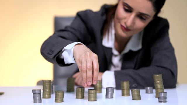 vídeos de stock e filmes b-roll de businesswoman stacking coins on table, delhi, india - vestuário de trabalho formal