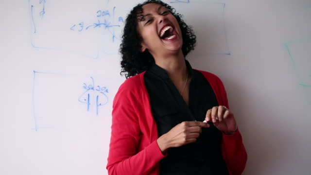 vidéos et rushes de ms businesswoman standing  against whiteboard holding pen laughing/washington, usa - sérieux