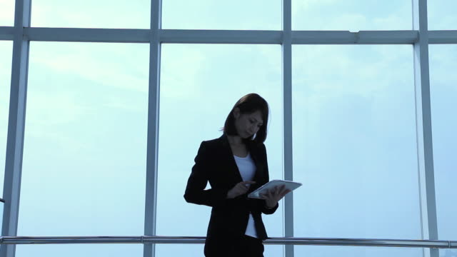 ms businesswoman standing and typing to mobile computing / odaiba, tokyo, japan - ビジネスウーマン点の映像素材/bロール