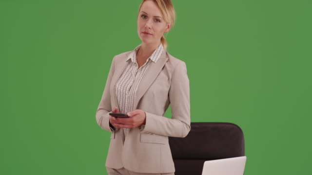 businesswoman standing at desk with smartphone on green screen. - sekretärin stock-videos und b-roll-filmmaterial