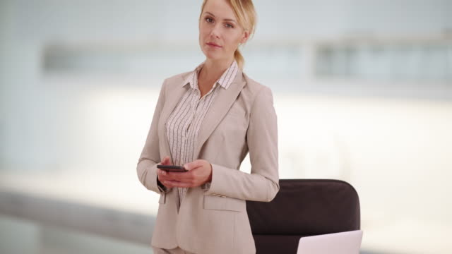 businesswoman standing at desk with smartphone - ladder of success stock videos & royalty-free footage