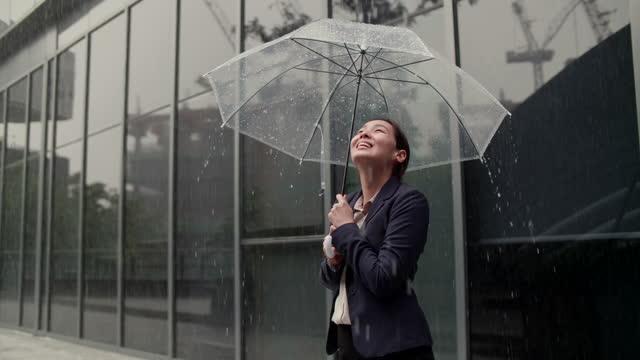 vídeos y material grabado en eventos de stock de empresaria de pie junto a la oficina mientras llueve - singapur