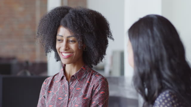 MS Businesswoman standing in discussion with laughing colleagues in office