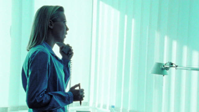 BLUE CANTED businesswoman standing in front of desk talking on phone + gesturing
