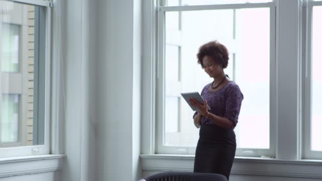 MS Businesswoman standing in office near window working on digital tablet