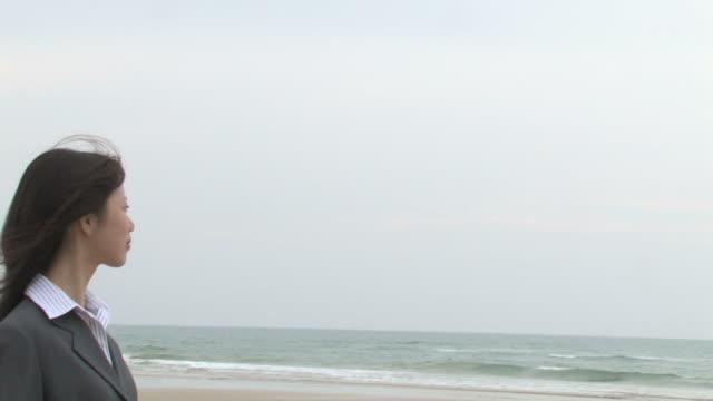pan businesswoman standing on beach - 横顔点の映像素材/bロール