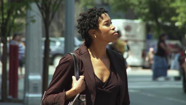 vídeos de stock, filmes e b-roll de ms businesswoman standing on street using mobile phone / new york city, new york, usa. - olhando ao redor