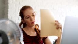 Businesswoman Sweating At Work With Broken Conditioner
