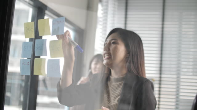 businesswoman take a planning and appointment on sticky notes attached to glass wall - building feature stock videos & royalty-free footage