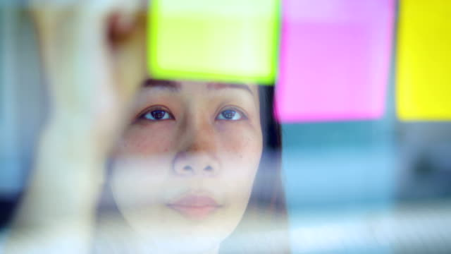 businesswoman take a planning and appointment on sticky notes attached to glass wall